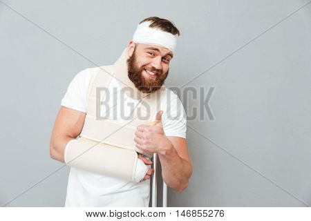 Portrait of smiling bandaged bearded young man standing with crutches and showing thumbs up gesture over gray background
