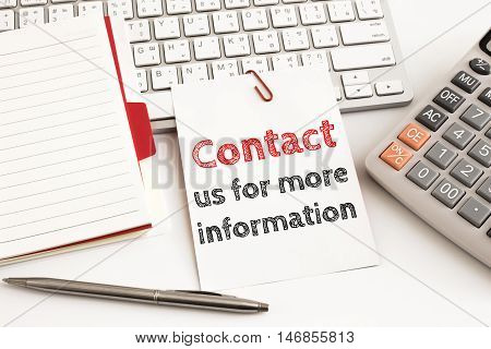 Word text contact us for more information on white paper card on office table / business concept