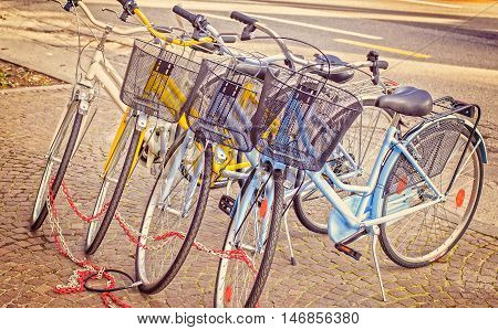 Four parked bicycles on the sidewalk chained together. Vintage style