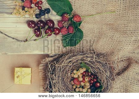 wild berries of red and white currant strawberry cherry blackberry and raspberry on wooden background and straw nest with golden gift box