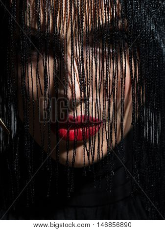 young sexy woman or girl with red lips on pretty face in beautiful feather hat brown color as halloween or carnival holiday costume and veil on grey background