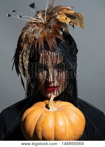 young sexy woman or girl with red lips on pretty face in beautiful feather hat brown color as halloween or carnival holiday costume and veil holds pumpkin on grey background