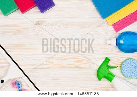 Cleaning items and tools lying on textured white floor background. Frame for cleaning concept or advertising. Empty copy space around products.