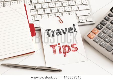 Word text Travel tips on white paper card on office table / business concept