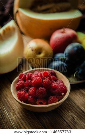 Assortment of fresh fruits and berries. Fruits plum apple pear melon. Berries red raspberries. Fruit bowl. Still life