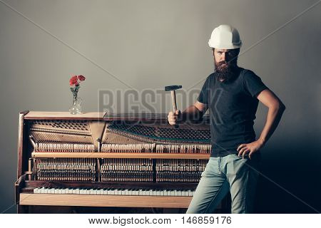 Man In Helmet Near Piano With Hammer