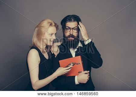 Astonished couple of young blond woman in black dress and handsome bearded hipster man in suit glasses with folder look in smartphone on grey wall