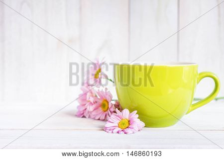 Cup of black coffee and daisy flowers on the white table