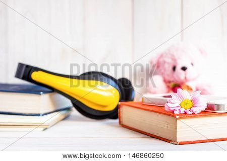 books or journal and Earphone with flowers arranged on a neutral white painted desk.