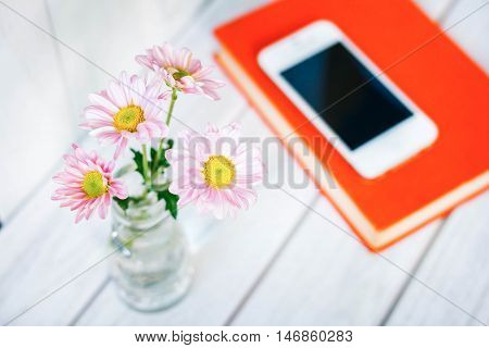 daisy flower in white vase  on the desk.