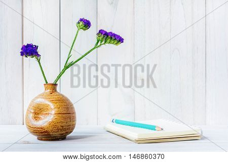 Blank notebook with flower on white wooden table