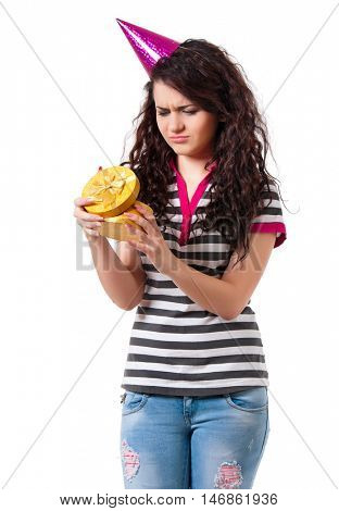 Beautiful unhappy girl with gift box, isolated on white background. Cute young woman in birthday cap holding present.