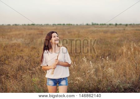 Young girl with long brown hair standing at the autumn meadow with spikelets in her hand and laughting. Selective focus warm tinted.
