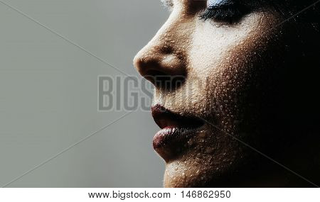 Beautiful woman with water drops and colourful makeup on young fresh face skin copy space on grey background
