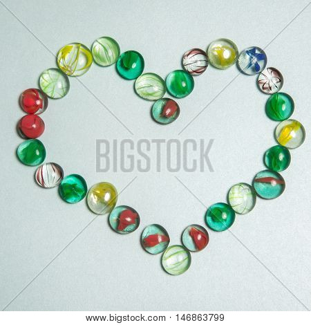 many colorful glassy or glass stones red yellow green and blue color laying in shape of heart as love valentines symbol on white background
