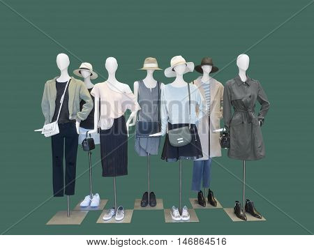 Group of female mannequins wear fashion clothing isolated on blue background. No brand names or copyright objects.