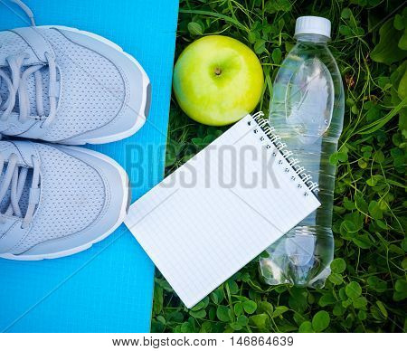 Sports shoes sneakers on yoga mat bottle of water and apple on fresh green grass. Sports in the open air. top view