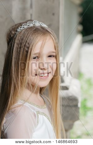 small girl kid with long blonde hair and pretty smiling happy face in dress and prom princess crown standing on sunny background closeup