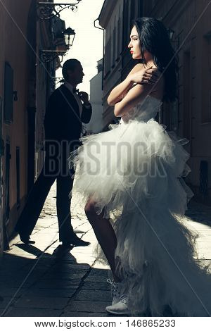 Beautiful bride in light and handsome groom in shadow married couple in wedding dress and suit pose outdoors on streetscape background