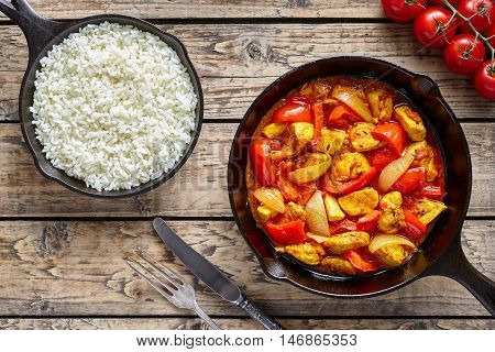 Chicken jalfrezi dietetic traditional Indian curry spicy fried meat with vegetables and basmati rice asian food in cast iron pan on vintage table background