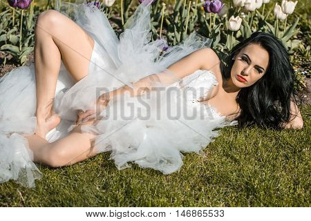 Sensual bride brunette woman in sexy fashion white wedding dress lies on grass in flowerbed on sunny summer day