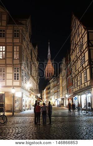 Hannover, Germany - September 9, 2016: Tourists exploring the old town district at night. Pedestrianized Kramerstrasse with its timber-framed houses and a view of Marktkirche church.