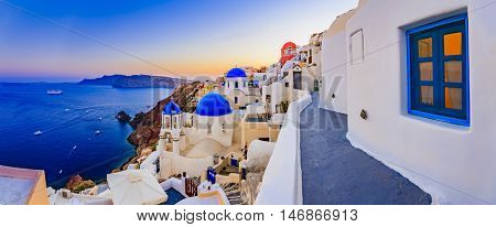 Amazing wide panorama sunset view with white houses on church with blue roofs in Oia village on Santorini island in Greece.