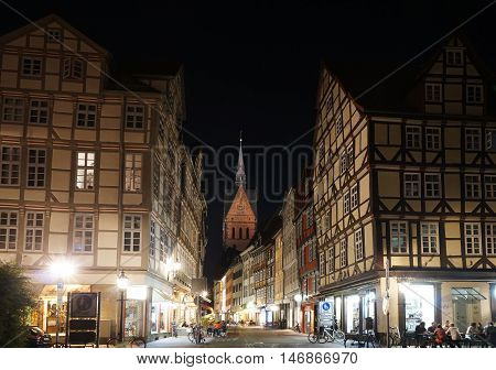 Hannover, Germany - September 9, 2016: Historic old town district with its half-timbered houses and a view of Marktkirche church at night.