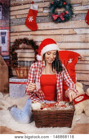 Young happy woman in red decomposes gifts. The concept of the New Year and Merry Christmas