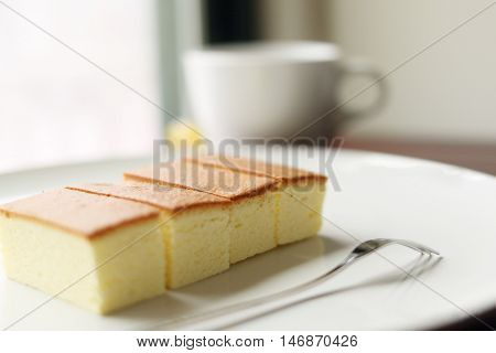 Sponge cake on plate in relaxing environment, selective focus