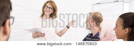 Shot of a smiling language teacher pointing hand to a board while standing in front of her multicultural class