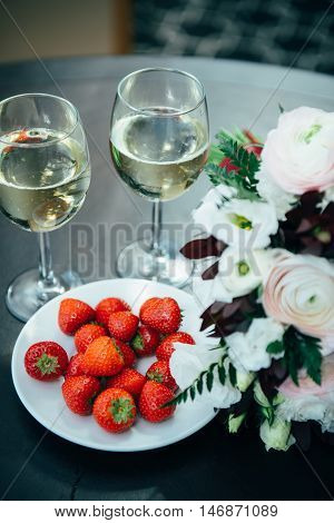 Prenuptial romantic morning. On the table there are glasses with champagne and strawberries.