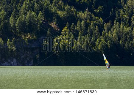 ALLEGHE,ITALY-AUGUST 22,2016:Man makes windsurfing on the beautiful lake of Alleghe between the Italian Dolomites.