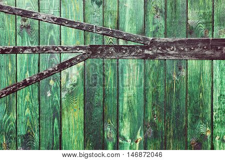 Old wooden gate planks with green color paint and black metal plate background.