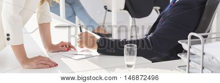 Sexy woman leaning against desk of her boss panorama