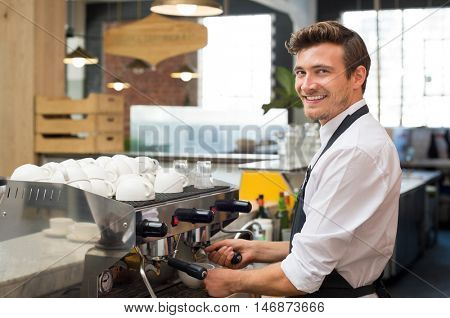 Happy waiter making coffee in machine while looking at camera. Portrait of smiling man working in his cafeteria. Happy waiter with apron preparing a cappuccino in a coffee shop.
