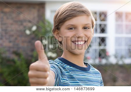 Happy young boy giving thumbs up sign. Smiling child showing thumbs up. Successful boy in casual showing thumbs up gesture and looking at camera.