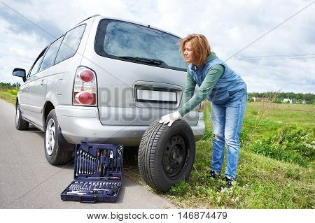 The woman changing a wheel of car