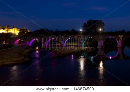 Old Bridge At Night With Lights And The Castle Of Carcassonne Behind