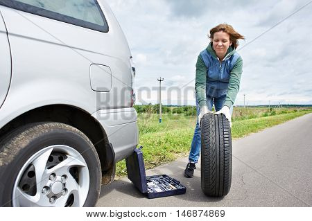 Woman Changing Wheel Of Car