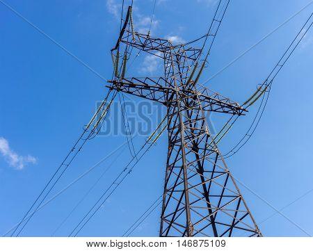 Power Line. pylon against a blue sky and sun.