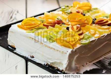 Cake with fruits and cream. Berries and pieces of apple. Appetite and health. Tasty layered dessert.