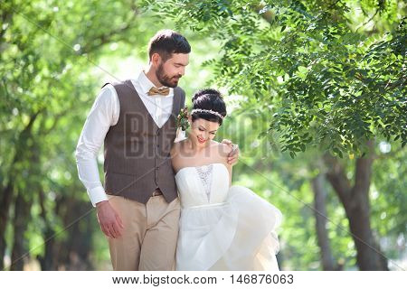 Groom and fiancee go for a walk to the garden hugging each other
