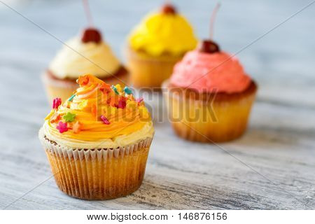 Cupcake with decoration. Cream of orange color. Appetizing and fresh sweets. Yummy for your tummy.