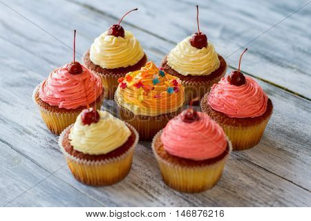 Cupcakes with bright frosting. Desserts on wooden surface. How about some sweets. Baked dough and buttercream.
