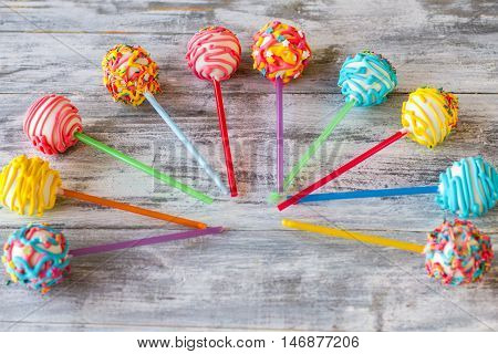 Bright-colored sweets on sticks. Candies with different glaze. Cake pops on gray table. Party for sweet tooth.