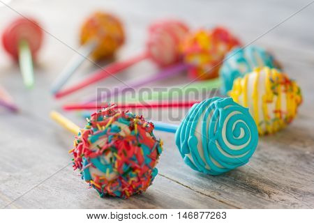 Colorful ball-shaped sweets. Candies on wooden surface. Holiday of taste. Custom made confectionery.