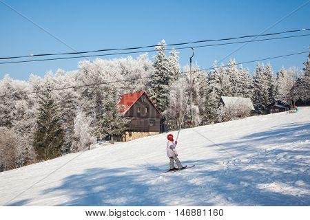 SKI CENTER KOHUTKA, CZECH REPUBLIC - JANUARY 16, 2010: Ski resort in the Czech Tatra. Frosty sunny winter day. Skier in a red helmet standing on the lift