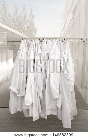 hanging farm lab coats in glasshouse wait for clean