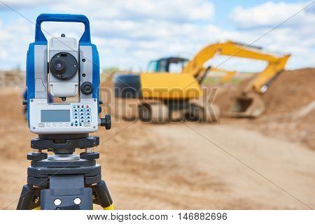 surveyor equipment theodolie at construction site with excavator